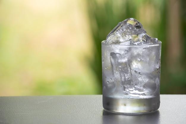 自然の背景を持つテーブル上のガラスのアイスキューブ