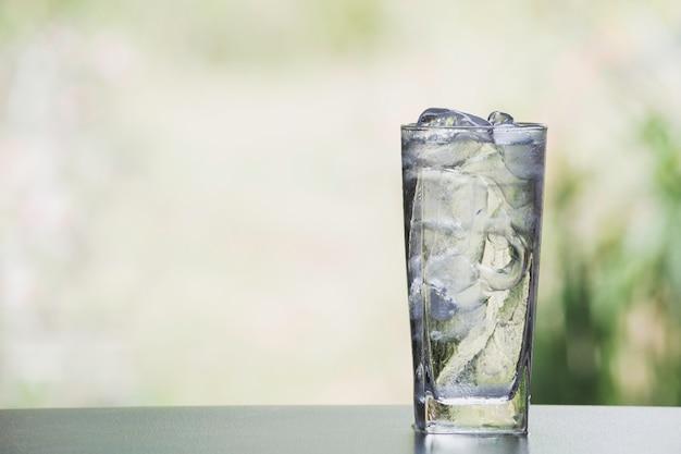 アイスキューブと自然の背景を持つテーブルの上のガラスの水