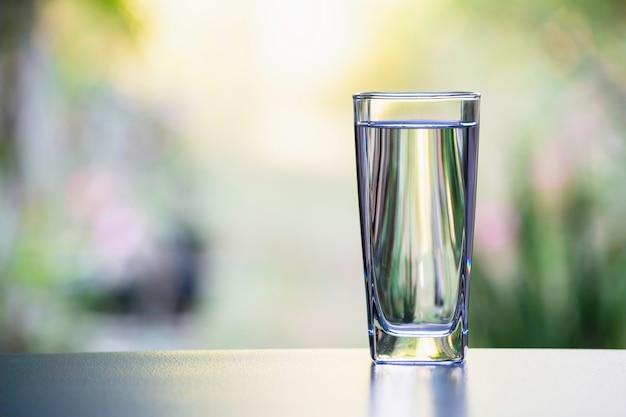 自然の背景を持つテーブル上のガラスの水