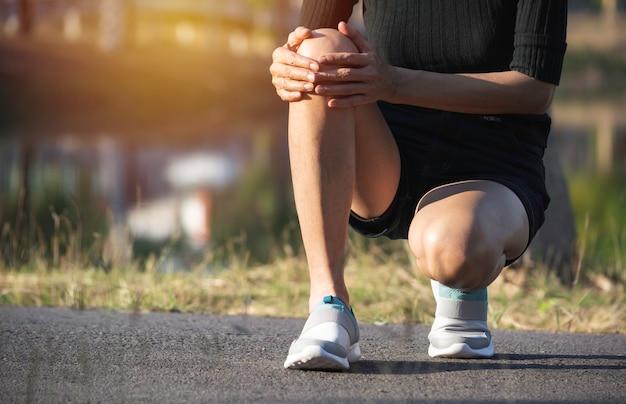 女性は悪い足にしがみついています。