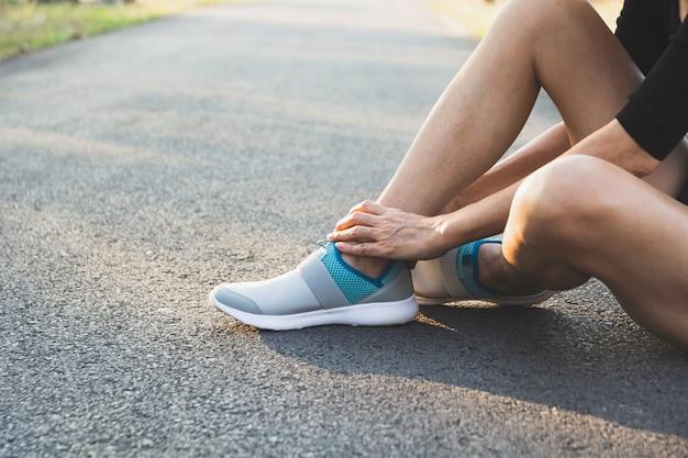 女性は悪い足にしがみついています。彼女の足の痛み。医療と痛みを伴う概念。