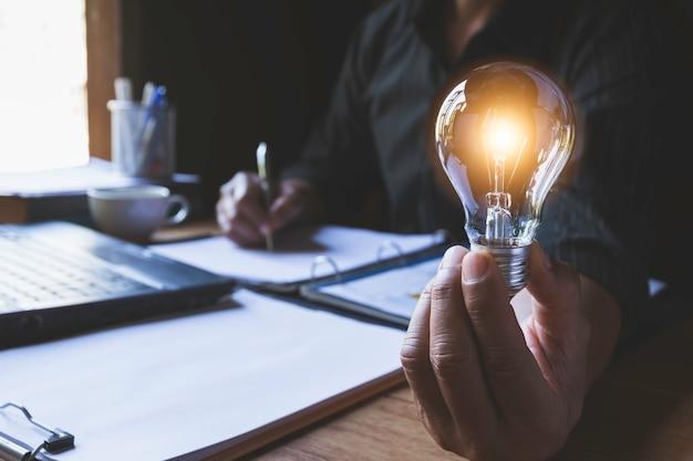 電球を押しながらアイデアと創造的な概念のために書く男性の手。