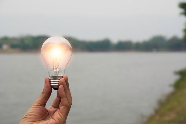 会計、アイデア、創造的な概念のための電球とコピースペースを保持している男性の手。