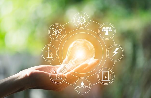 エネルギーのための電球とコピースペースを保持している男性の手