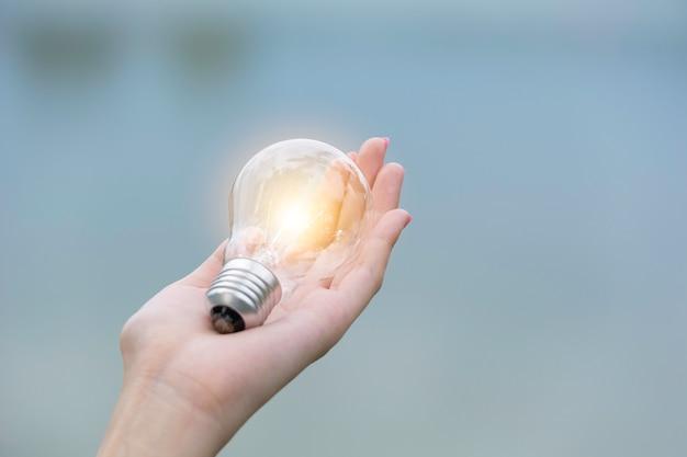 イノベーションと手の創造的な概念は電球を保持します
