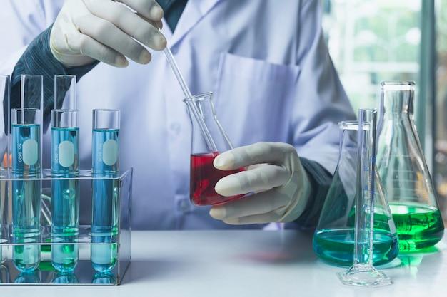Исследователь со стеклянными лабораторными химическими пробирками с жидкостью