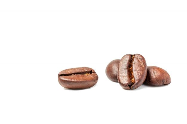 白い背景とコピースペースに分離されたコーヒー豆の広がり
