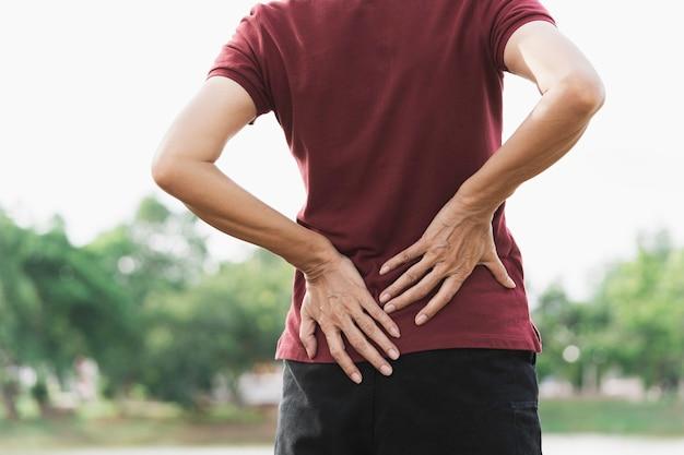 Женщина страдает от боли в спине, травмы позвоночника и проблемы с мышцами на открытом воздухе.