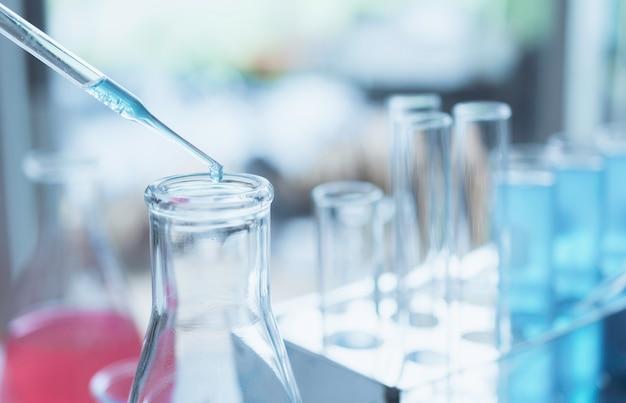 分析、医療、製薬、科学研究の概念のための液体のガラス実験室化学試験管を持つ研究者。