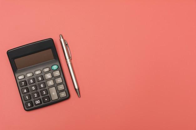Черный калькулятор с ручкой и копией пространства.