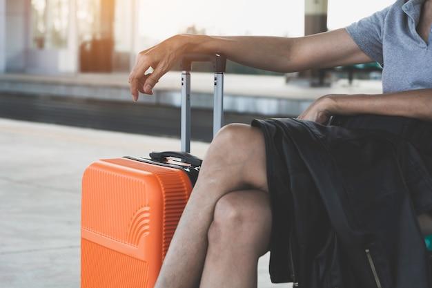 Женщина с оранжевым чемоданом багажная сумка, сидя на вокзале.