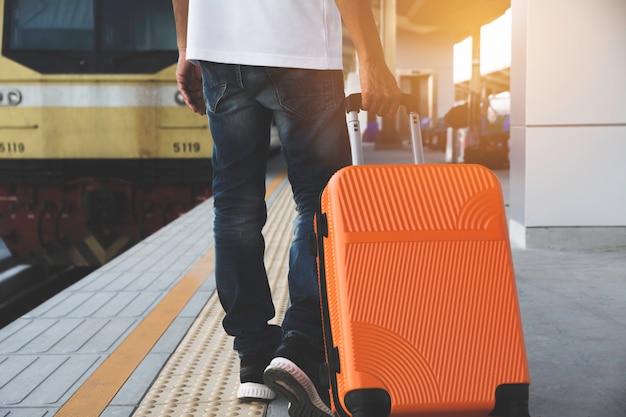Человек, перетаскивая оранжевый чемодан багажная сумка, ходить на вокзале.