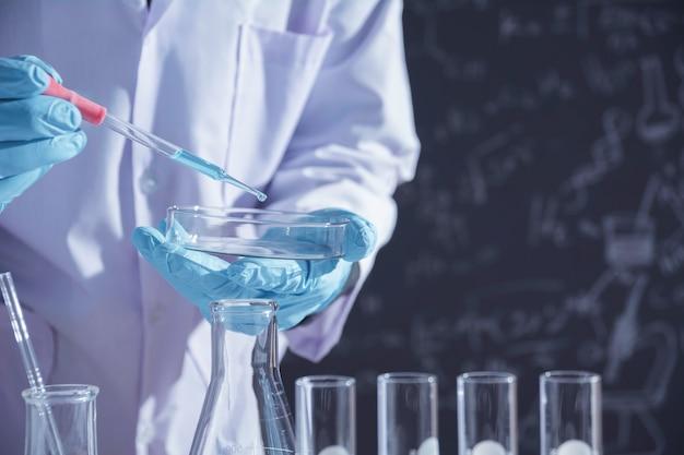 分析、医療、製薬、科学研究用の液体を含むガラス製実験室化学試験管を持つ研究者。