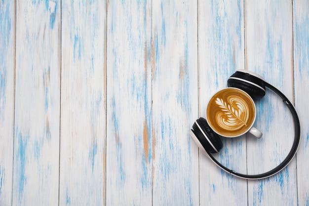 木製のテーブルの上にヘッドフォンとコーヒーのカップ。コピースペースでコーヒーカフェラテアートの平面図です。ドリンクとアートのコンセプト。