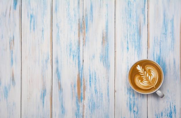 木製のテーブルの上のコーヒーカップ。コピースペースでコーヒーカフェラテアートの平面図です。ドリンクとアートのコンセプト。