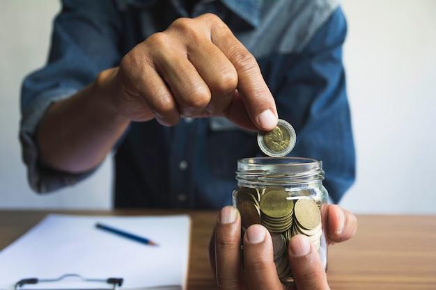 手はビジネスのためのガラスの瓶にコインをドロップします。財務および会計の概念。