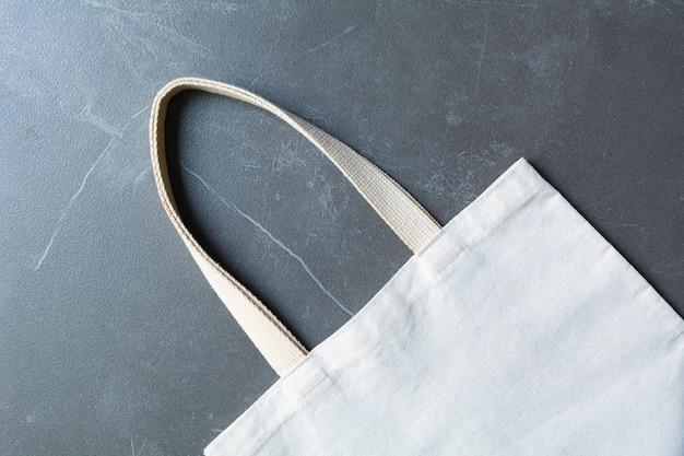 白いトートバッグのキャンバス生地。コピースペースを持つ布ショッピング袋モックアップ。