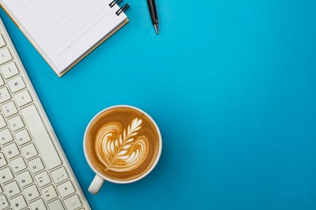 青いテーブルの上のキーボードとコピースペースでコーヒーカップ。オフィスデスクとドリンクのコンセプト。