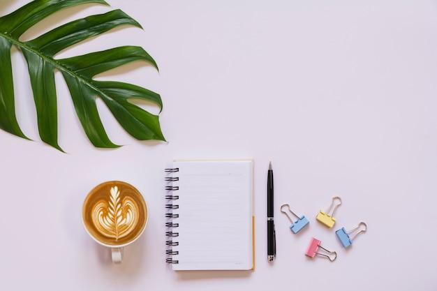 白いテーブルの上のメモとコピースペースでコーヒーカップ。オフィスデスクとドリンクのコンセプト。