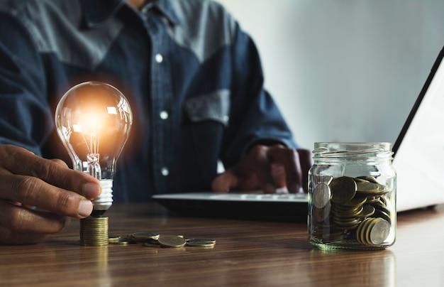会計、アイデア、創造的な概念のためのコインお金とコピースペースと電球を保持している男性の手。
