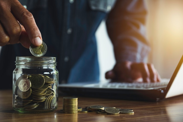 ビジネスのために成長しているお金コインスタックでコインを手ドロップします。財務および会計の概念。