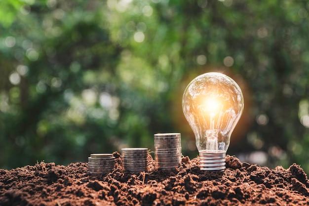 Концепция денег сбережений с стогом и электрической лампочкой монетки денег.