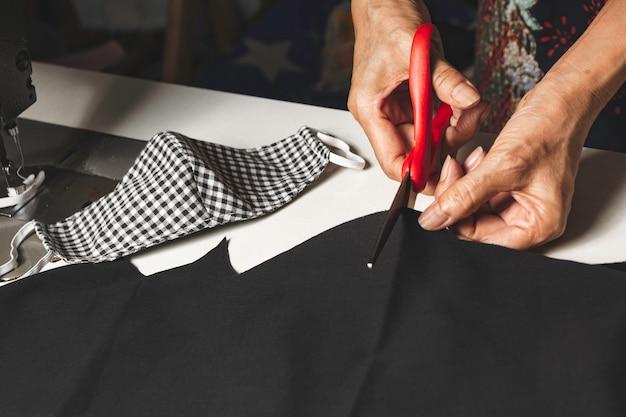 Женщина резки черной ткани с помощью ножниц. концепция работы по дому и образ жизни.