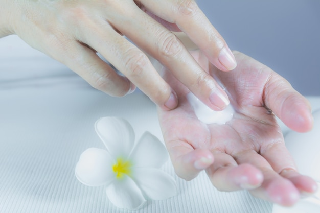 女性の手はローションを白いテーブルのローションボトルで手の皮膚に塗布する。