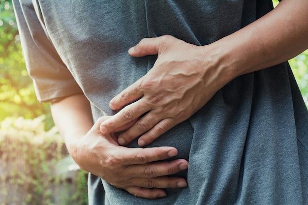 Муж, страдающий от боли в желудке, боль в животе на открытом воздухе, здоровая концепция.