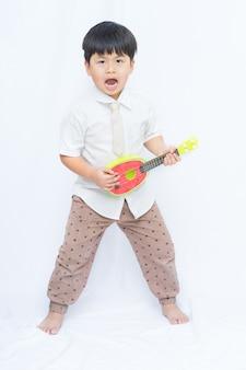Симпатичные азии мальчик, проведение гитары на белом фоне, портрет мальчик откройте рот,