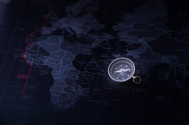 世界地図の色の黒の背景にコンパス、