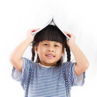 白い背景に彼女の頭の上に本を持つ少女。