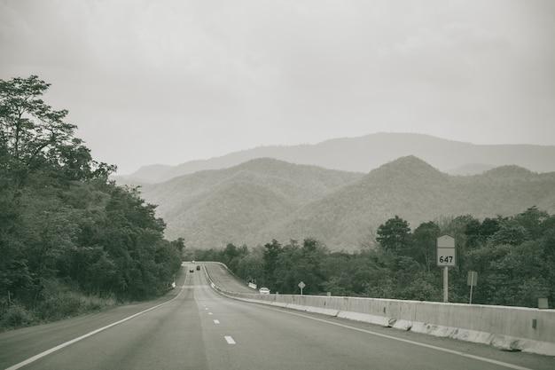 黒と白の田園地帯のもや高速道路写真のマウンテンビューと長い直線道路