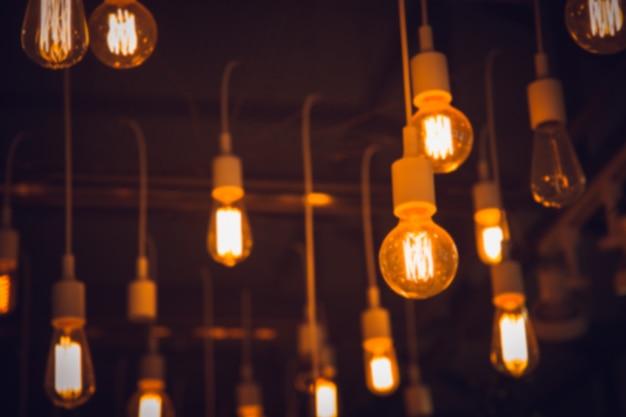 ぶら下がっている電球のインテリアカフェの照明をぼかし