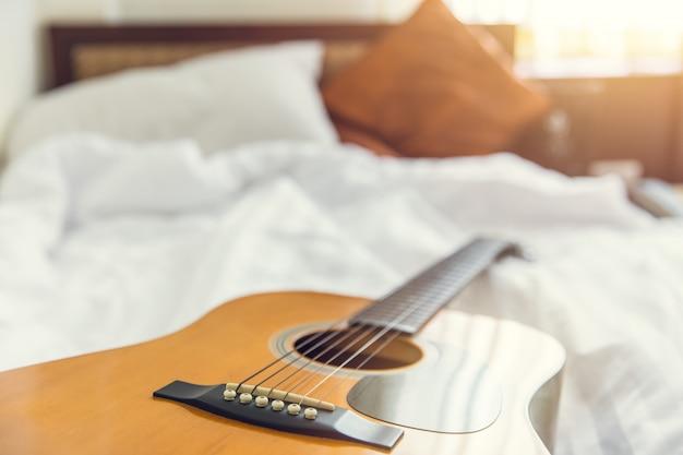 白いベッドで寝室の朝コンセプトギターの音楽