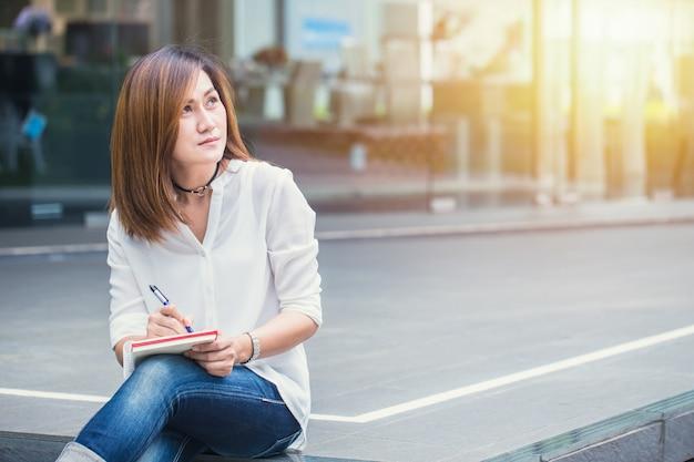 アジアの女性のペンを書くと屋外の手でメモを書くビジネスプロジェクトのアクションを考える
