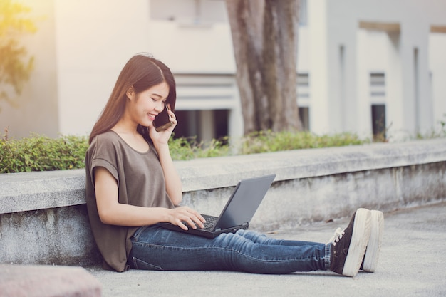 Технологии современного образа жизни, азиатские милые подростки, звонящие со смартфона и использующие ноутбук, наслаждаются счастьем и улыбкой в кампусе
