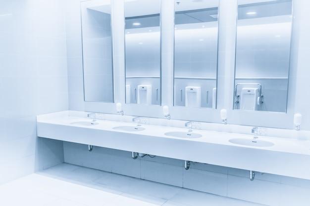 バスルームの清潔で新しいモダンインテリアトイレのシンク行青い色調水ハンドシャワー