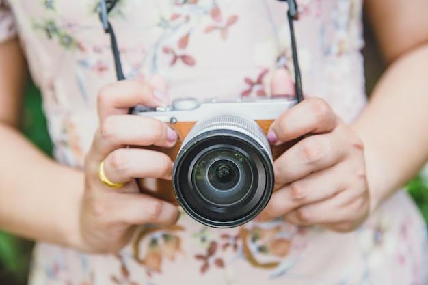 インディ女性はミラーレスカメラレトロビンテージスタイルのデジタル写真家を保持します。