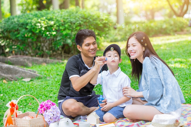 お父さんお母さんと息子は緑豊かな公園でピクニックの家族の休日をお楽しみください