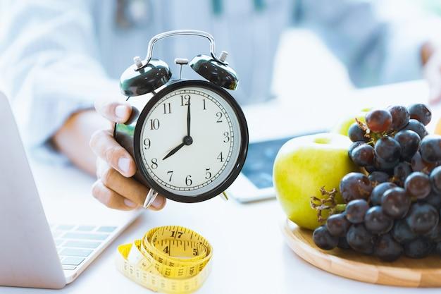 ヘルスケアまたはダイエット食品アドバイザーの時間は、健康食品とコンセプトであなたの健康を計る時計を表示します。