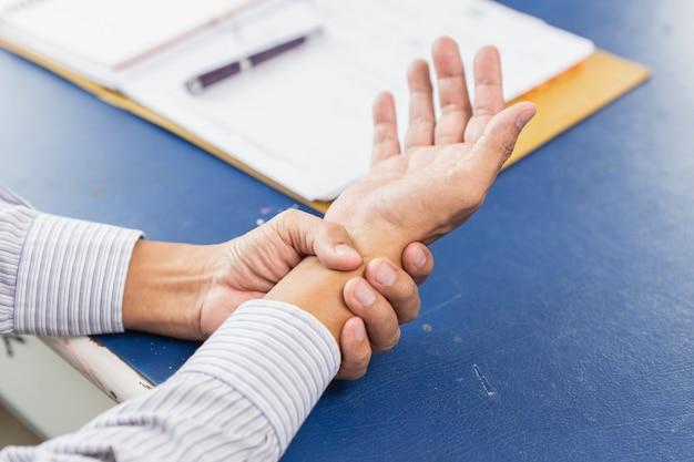 痛みを伴う手首のクローズアップハンドホールドマッサージリリーフの痛み
