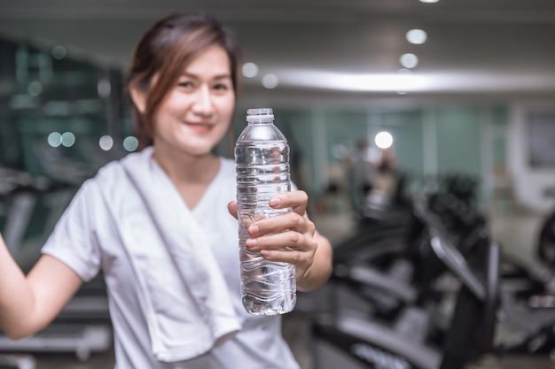 健康的なアジアの女性の手を保持スポーツクラブの背景を持つ飲料水のショーボトル