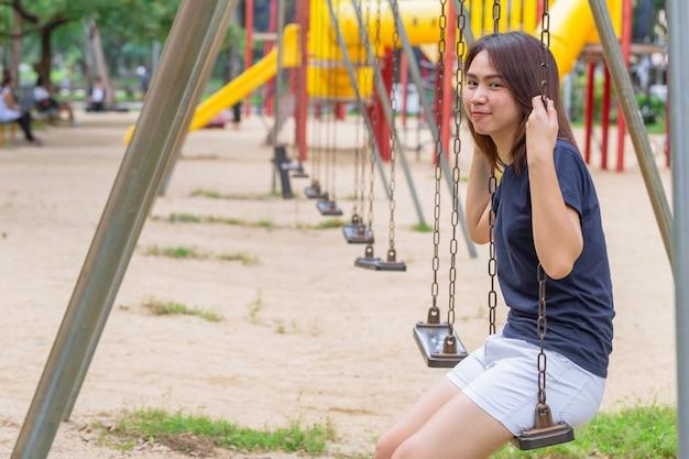 公園のブランコに座っているアジアのティーン