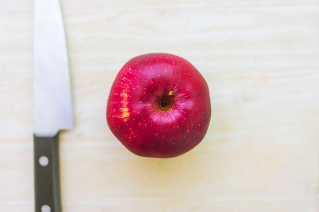 Свежее красное яблоко на дереве с кухонным ножом сверху
