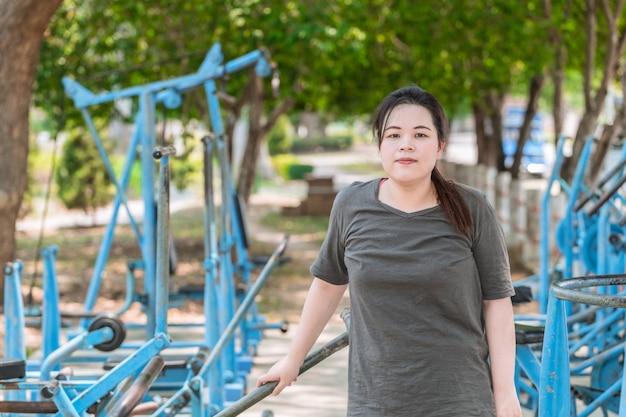 ダイエットフィットネスの概念のための運動マシン屋外公園に立っているアジアの脂肪の女性の肖像画