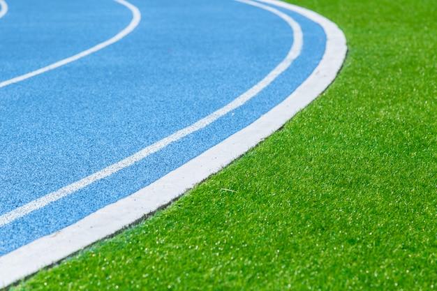 運動の背景のスポーツスタジアムで緑の草とランニングトラック