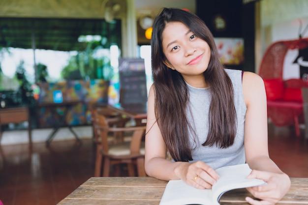 Азиатка подросток улыбка чтение книги красивая милая счастливым наслаждаться с образованием в кафе