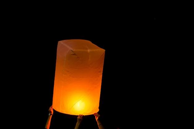 Люди выпускают бумажную лампу огня, повышающуюся ночью на фестивале лой кратонг в таиланде