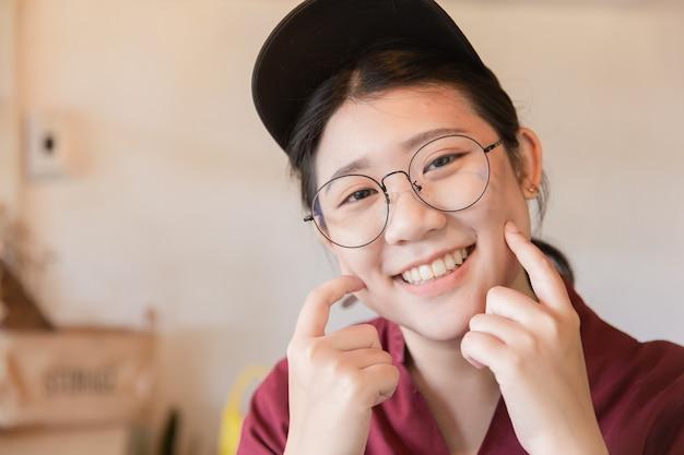 Пухлая пухлая молодая симпатичная белая улыбка зуба азиатская молодая студентка с очками и шляпой трогает пальцем щеку с копией пространства
